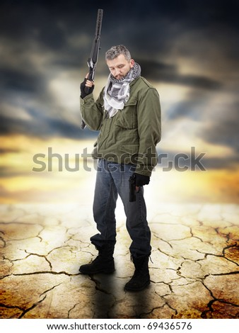 Military standing and looking down, in background apocalyptic sunrise - stock photo