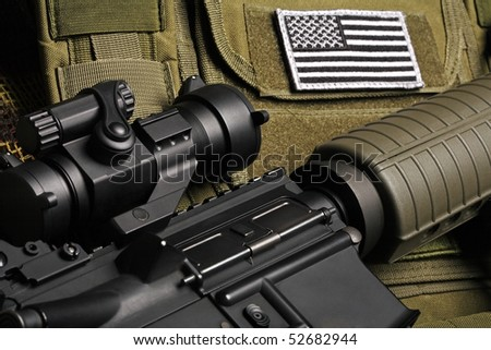 Military still life. Tactical vest with U.S. battle flag and assault rifle close-up. - stock photo