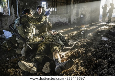 "MILITARY TRAINING ZONE, ISRAEL - DECEMBER 8, 2015: Two Israeli heroic combat medics saving the life of an Israeli ""wounded"" soldier during military training. Dramatic light shines on wounded warrior."
