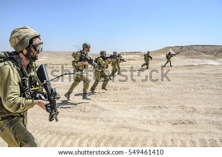 MILITARY TRAINING ZONE, ISRAEL - JUNE 17, 2015: Israeli army combat commando squad firing while charging on terror targets. Infantry soldiers running & shooting during desert military combat training.