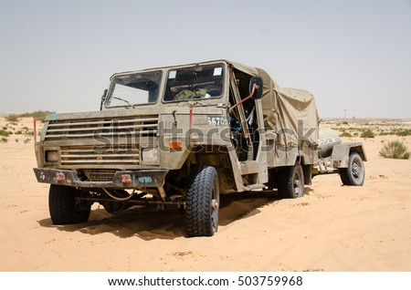 MILITARY TRAINING ZONE, ISRAEL - JUNE 5, 2013: Israeli army supply truck standing in the desert sands. Old military truck parking in dunes. Military logistics vehicle standing.