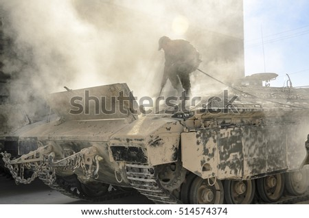 MILITARY TRAINING ZONE, ISRAEL - OCTOBER 20, 2014: Israeli soldier standing on tank. Israeli armored vehicle crew member extinguishing fire smoking from tank's burning engine. Soldier cleaning tank.