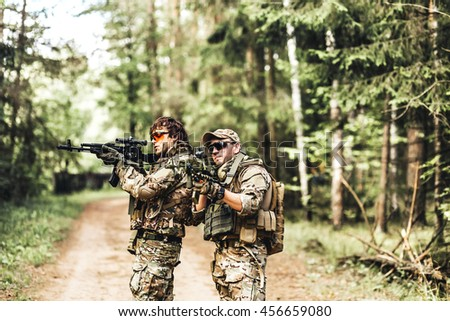 military. Two Armed man in a zone of armed conflict soldier in uniform targeting with assault rifle outdoors. two solders with weapon - stock photo