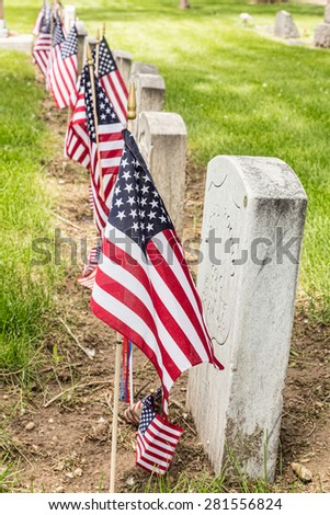 Military Veteran cemetery tombstones view with United States of America red, white and blue flags.  - stock photo