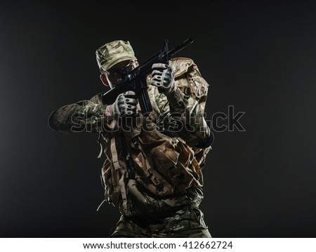 Military, war, conflict, soldiers - Special forces soldier man hold Machine gun on a  dark background. Soldier takes aim. Military equipment NATO soldiers - stock photo