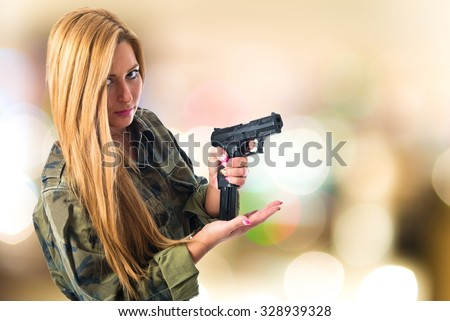 Military woman carrying a gun on unfocused background - stock photo