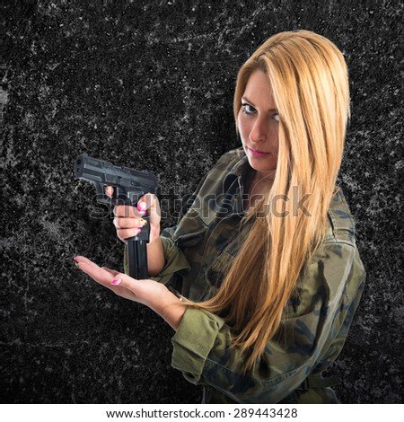 Military woman carrying a gun over textured background - stock photo