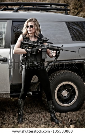 Military Woman wearing Tactical Gear and Holding an AR15 Gun. - stock photo
