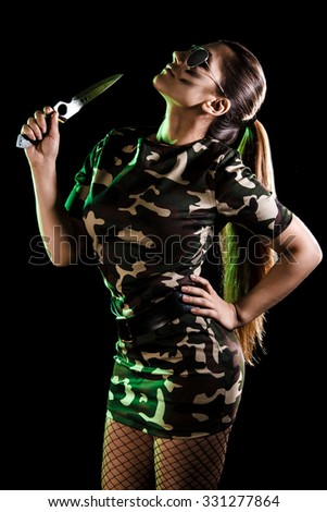 Military woman with a knife over black background