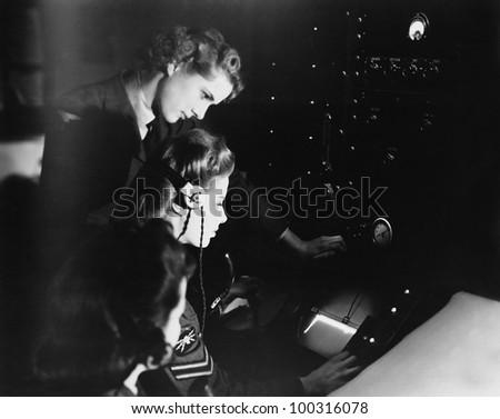 Military women using communications equipment - stock photo