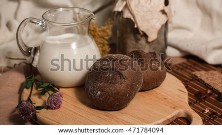 Milk and bread, Rye buns and clover on wooden desk. Food photo. Healthy Breakfast.