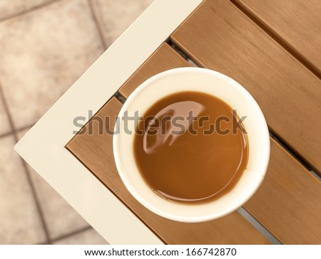 Milk and coffee in disposable paper cup on wood table. View from above. Tile floor. Nice for fast food concept. Horizontal photo. - stock photo