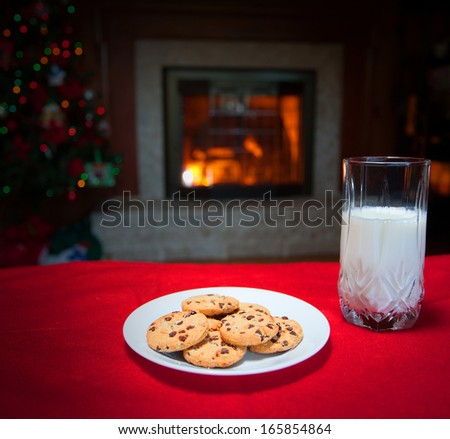 Milk and cookies laid out in front of a fireplace and Christmas tree - stock photo