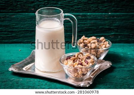 Milk and muesli on wooden table - stock photo