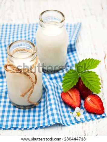 Milk and strawberries on a wooden background