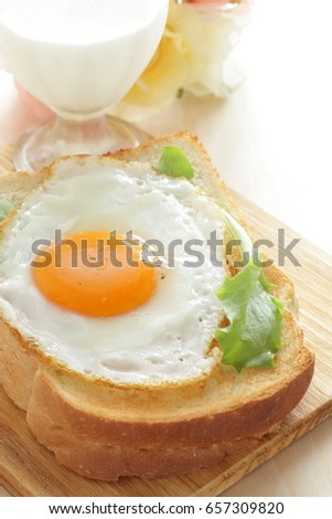 Milk and sunny side up fried egg on toast