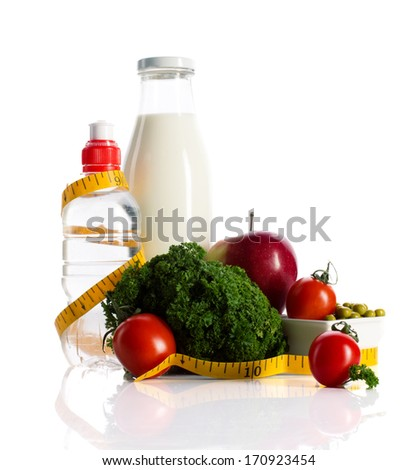milk and water in bottles, apple, tomato, green peas, curly salad and measure  on white background - stock photo