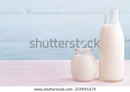Milk and yogurt from right side light blue background - stock photo