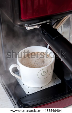 Milk being served in the preparation of a cappuccino in espresso machine.