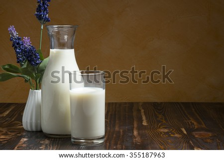 Milk bottle and milk glass put on wooden table, selected focus, shallow DOF