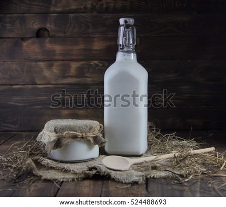 milk bottle  and sour cream with a wooden spoon