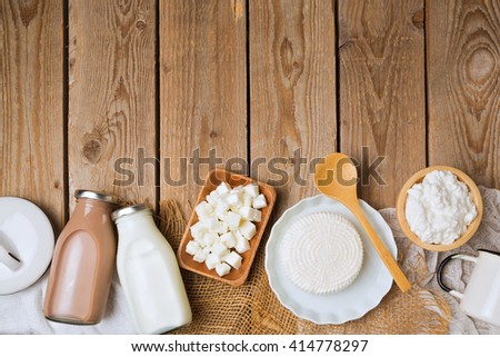 Milk bottles and cheese on wooden rustic background. View from above. Flat lay