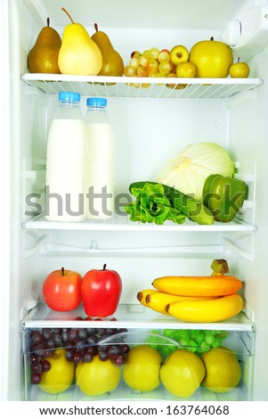 Milk bottles, vegetables and fruits in open refrigerator. Weight loss diet concept. - stock photo