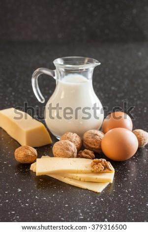 milk, cheese, eggs and nuts on a table, selective focus