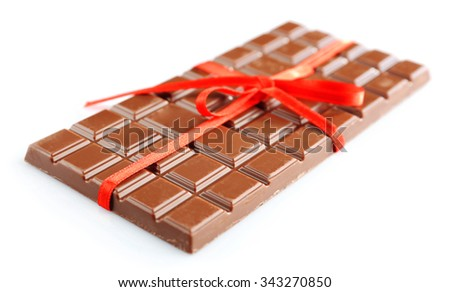 Milk chocolate bar with red bow on color wooden background - stock photo