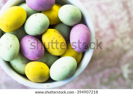Milk chocolate easter eggs in cup seen from directly above. - stock photo