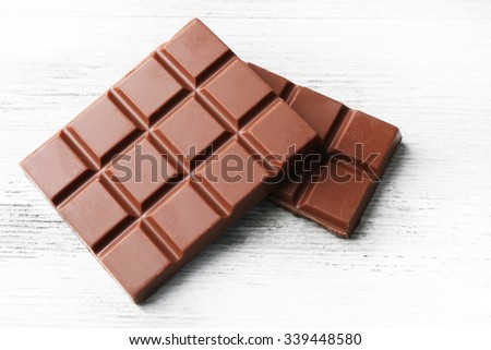 Milk chocolate pieces on color wooden background - stock photo