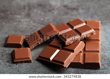 Milk chocolate pieces on gray background - stock photo