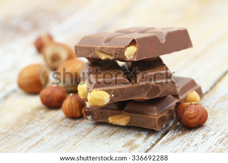 Milk chocolate pieces with whole hazelnuts on rustic wooden surface  - stock photo