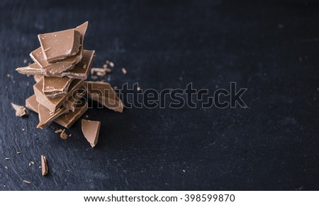 Milk Chocolate (selective focus) on a slate slab (close-up shot) - stock photo