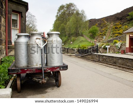 Milk churns at Goathland railway station, Yorkshire, England. - stock photo