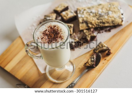 Milk cocktail with chocolate cookies on table close-up