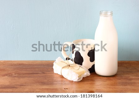 milk cup an butter on wooden table  - stock photo