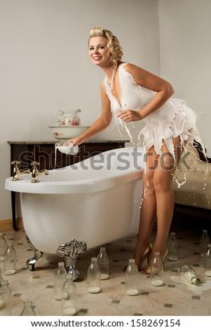 Milk dress pin-up girl preparing her bath - stock photo