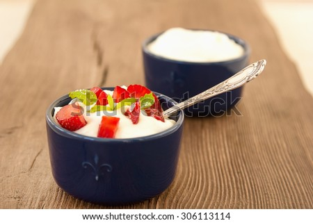 Milk fruit dessert. Whipped cream with strawberries. Serving tasty treats from dairy cream and red strawberries standing on the wooden table. Blue cup with cream and a silver spoon. Berries and cream. - stock photo