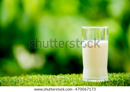 milk glass on grass with nature background
