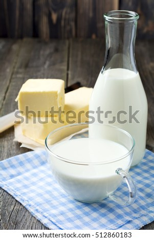 Milk in a cup and milk products on a dark wooden background. Selective focus.Rustic style.