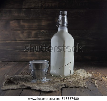 milk in a glass bottle and a bucket on wooden background