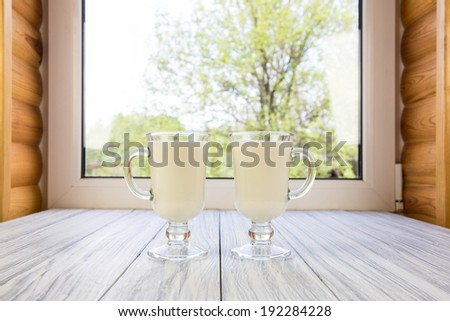 Milk in a glass cup against a window - stock photo
