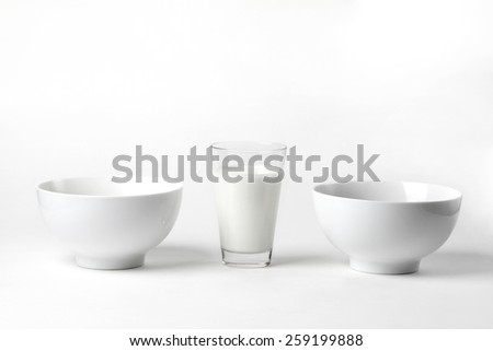 milk in a glass - white fresh organic cow's milk in a glass painted in the studio on a white background and two white ceramic bowl for cereals - stock photo