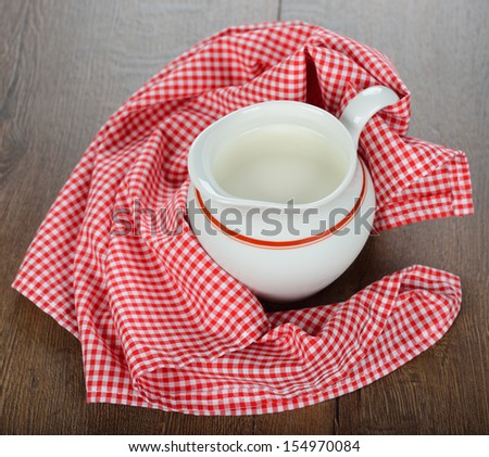 Milk in a jug on a brown table - stock photo