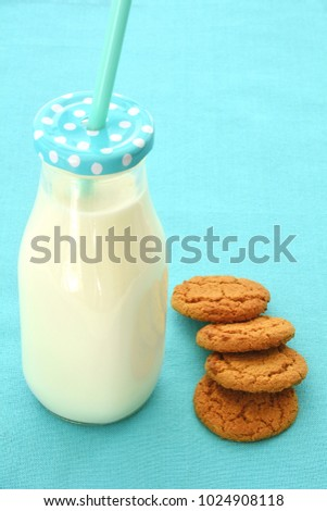 Milk in glass bottle with ginger cookies in vertical format with room for text