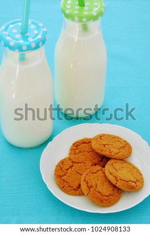 Milk in glass bottles with ginger cookies in vertical format and shot in natural light