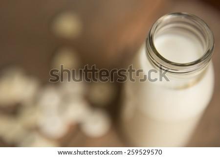 Milk in glass bottles with milk pellets Depth of Field style - stock photo