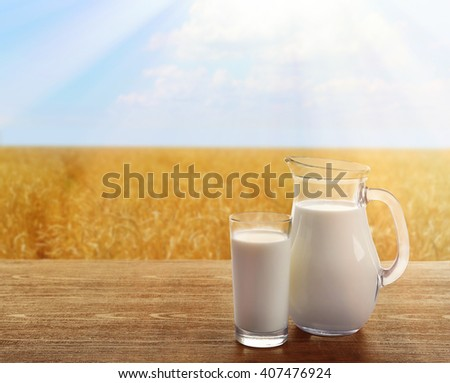 Milk in glassware on sunny nature background - stock photo
