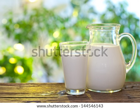 Milk in jar and glass on the old wooden table on a outdoor setting.